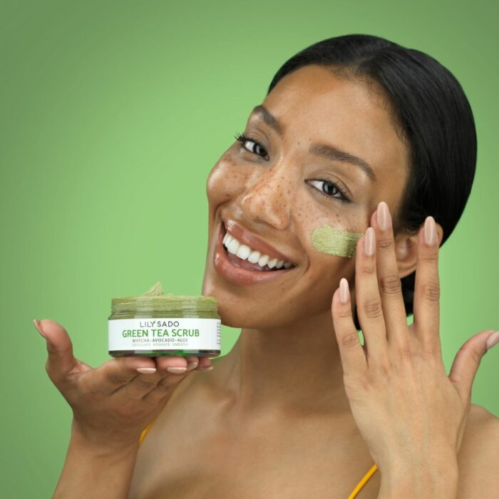Model is showing a smear on her face against a green background