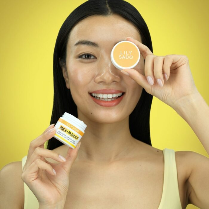 model holds the cap in front the eye against the yellow background
