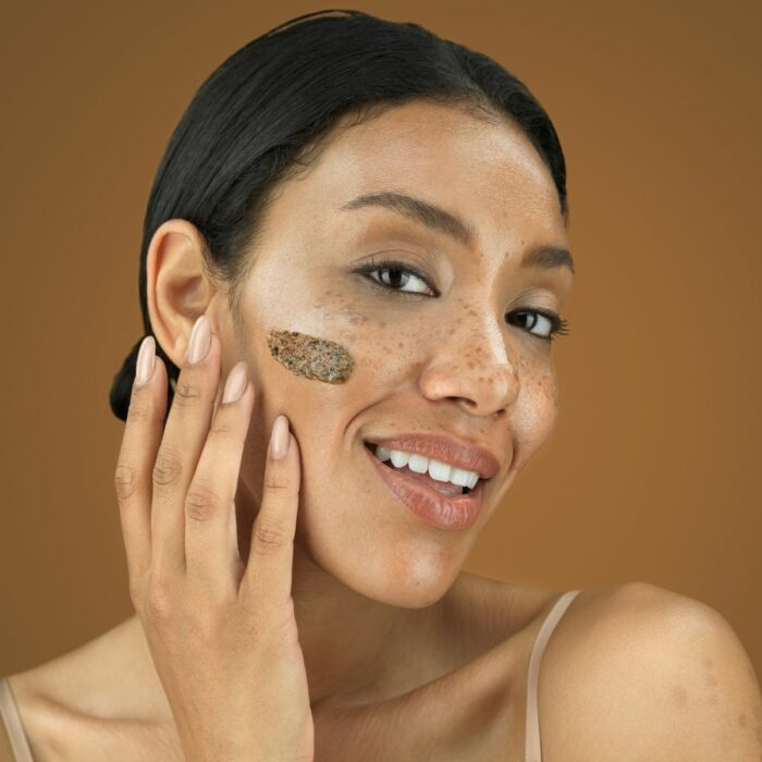 Model with a swatch on the face posing on a mocha background