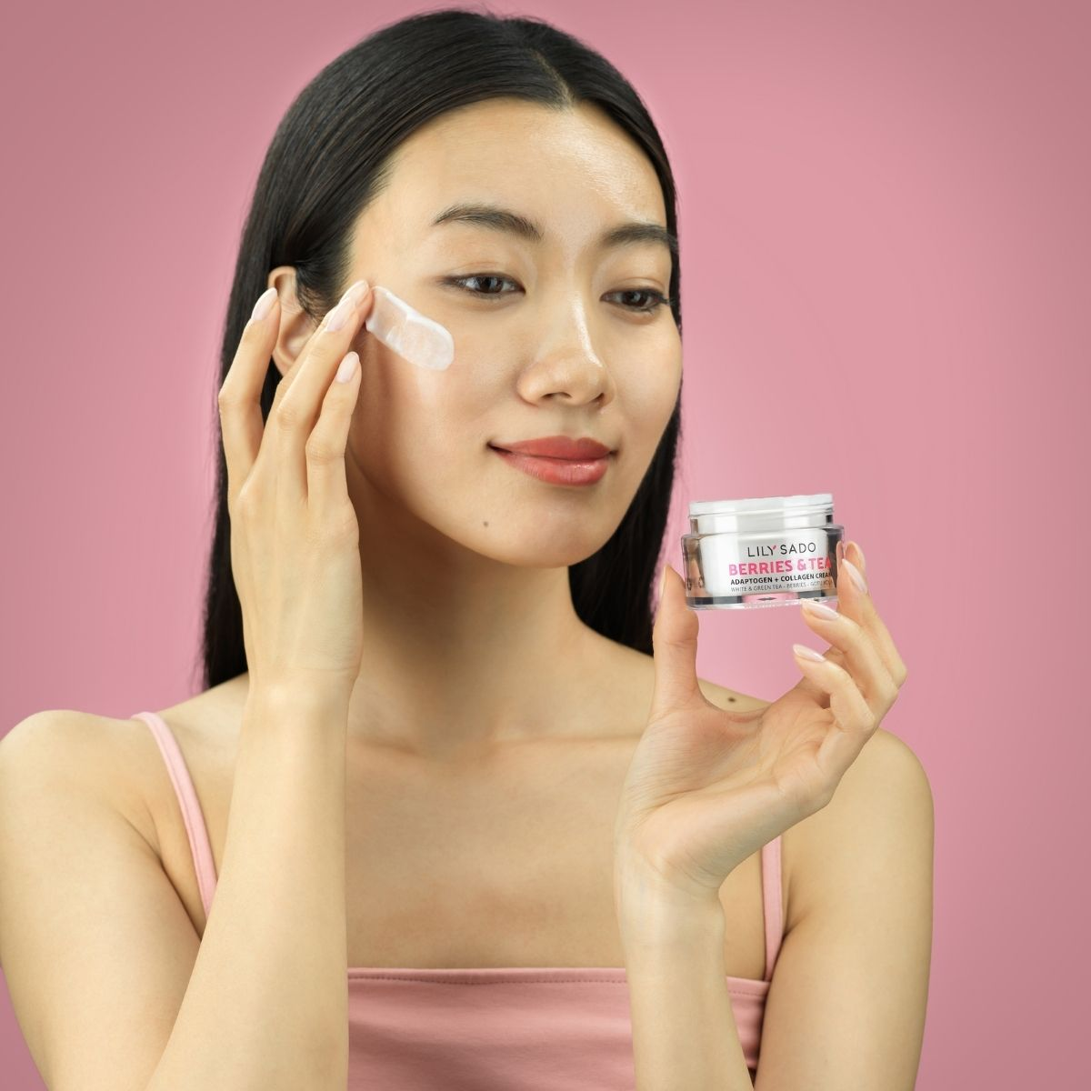 Asian model with cosmetics on a pink background showing the product