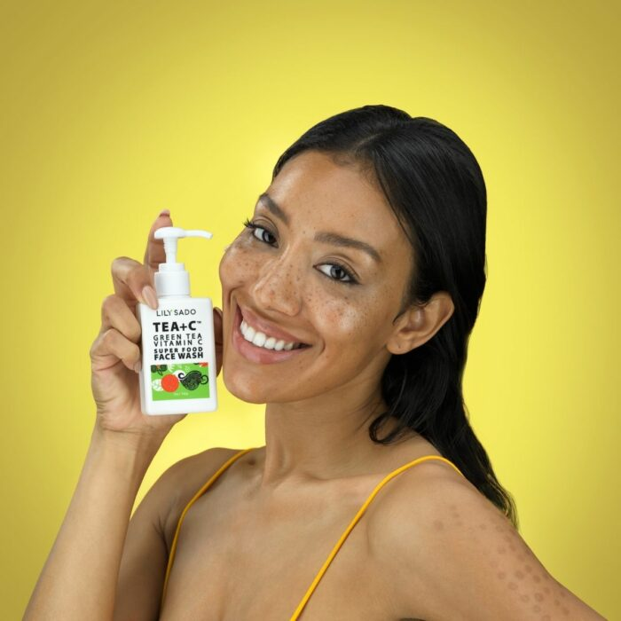 Afro-American Model is showing a smear of a beauty product on her face against a yellow background